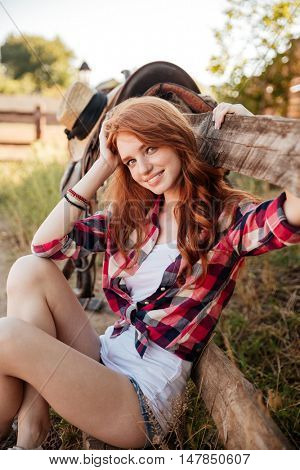 Portrait of cheerful cute young woman cowgirl siting on farm