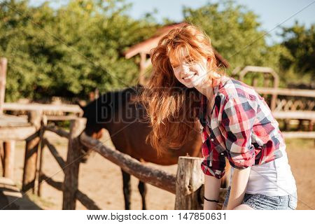 Smiling redhead young woman cowgirl sitting on fence in village