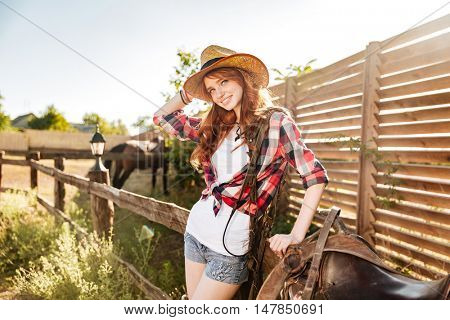Portrait of happy beautiful young woman cowgirl in hat on ranch