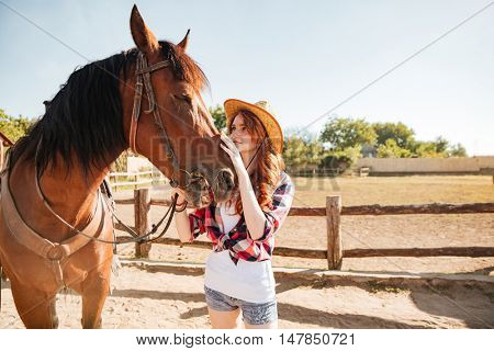 Cute redhead young woman cowgirl standing and taking care of her horse in village