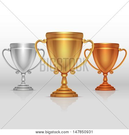 Gold, silver and bronze winners cup, goblet vector. Set of sports trophies to the winners illustration