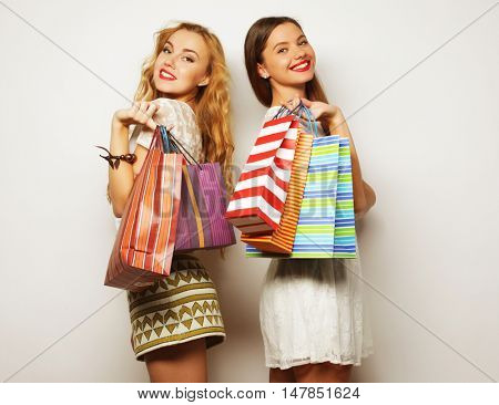 Gorgeous girlfriends with paperbags looking at camera