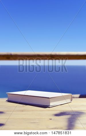 closeup of a book with a gray cover on a wooden table outdoors, with the ocean in the background