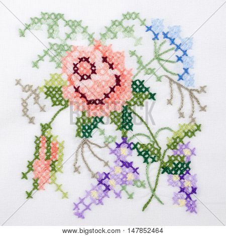 Flowers motif hand embroidery on white linen tablecloth.  Multicolored cross stich decoration with yarn. Handicraft. Macro photo close up from above.