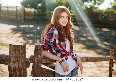 Happy charming young woman cowgirl standing and relaxing on ranch