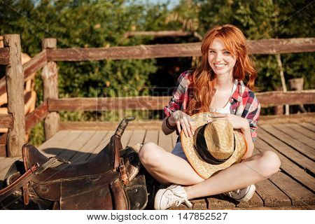 Happy beautiful young woman cowgirl with hat sitting on ranch