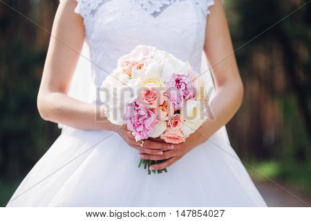 Bride's bouquet in her hands. Beautiful wedding bouquet in hands of a bride. Selective focus. Young bride holding the wedding bouquet