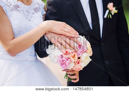 Hands and rings on wedding bouquet together