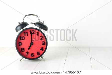 Red Morning Alarm Clock pointing at 7:00 with copyspace