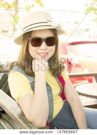 Beautiful woman wear white hat and sunglasses smile with happiness feeling (Soft color tone)