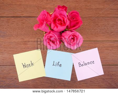 Handwriting word Work Life Balance on notepaper and pink rose flower with wood background