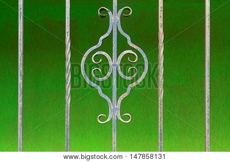Old wrought-iron lattice on a green background. Architecture