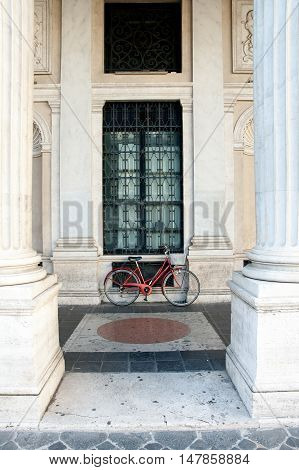 Red bicycle with nobody near parked under architectural colonnade hall