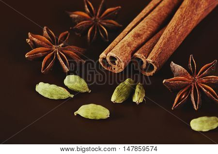 two cinnamon sticks three stars anise and a cardamom on a brown background close-up horizontal