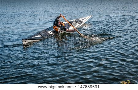 man rolling with a kayak on a lake - serial pictures 10 of 11