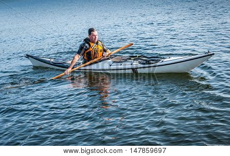 men back on surface of the lake from rolling with a kayak - serial picture 11 of 11