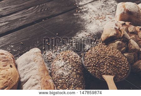 Bread border on dark wood background. Brown and white whole grain loaves still life composition with wheat flour sprinkled around. Bakery, cooking and grocery store concept.