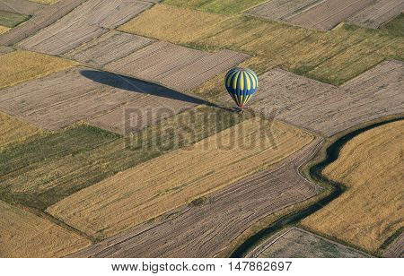 Multicolored air-balloon touchdown on fields. Aerial view.