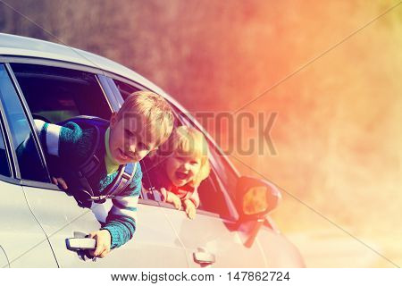 happy little boy and girl travel by car in autumn nature