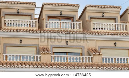 small balconies with railings and balusters in the yellow apartment building and the tiles on the roof in the seaside town