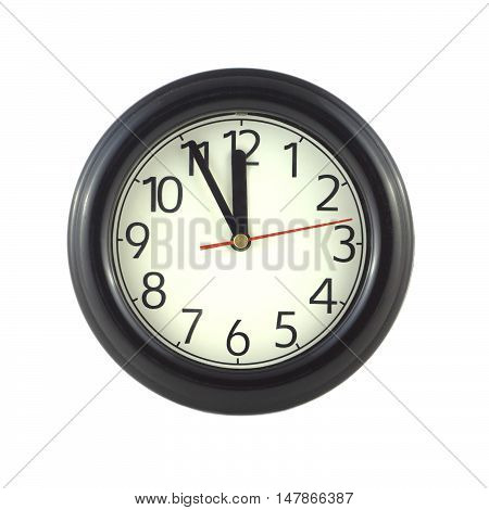 Big round wall clock shows almost twelve isolated on white close up