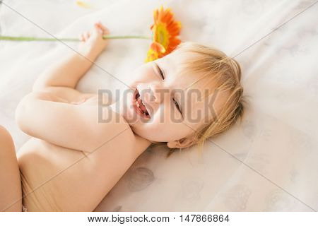 little girl lying on the bed and plaing whith flower