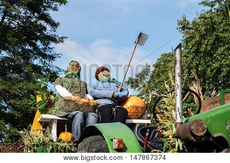 scarecrow straw figures farmer and farmer's wife sitting on an old tractor at the harvest festival thanksgiving on a sunny day with blue sky