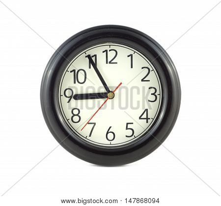 Big round wall clock, with a dark rim on a white background close-up and arrows showing five minutes to nine o'clock