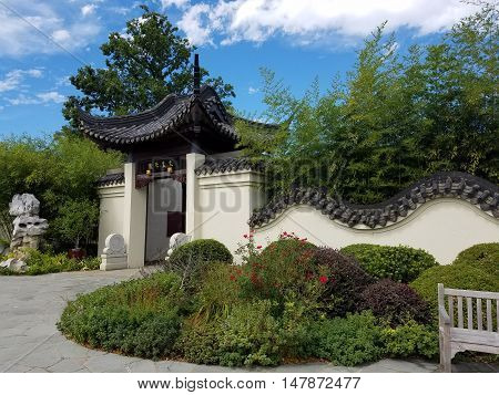 Beautifully landscaped entry to a Chinese garden with traditionally decorative walls and gate