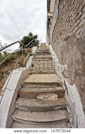 Old stairs with cracked uneven concrete stairs goes up