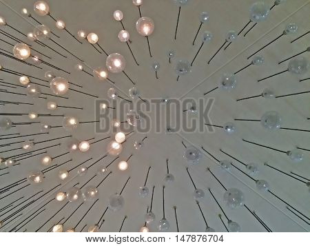 Blurry background of partially soft lit ceiling lamps