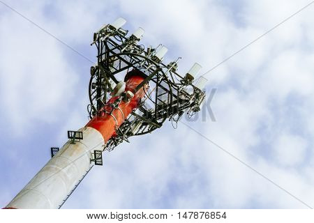 Cell Phone Antennas On A Red And White Tower