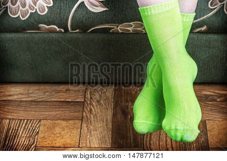 foot overhang from the sofa in green socks. vignette for artistic effect