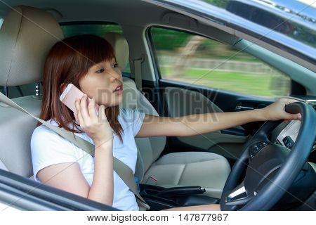 Woman driving fast a car distracted on the phone and looking on the way.