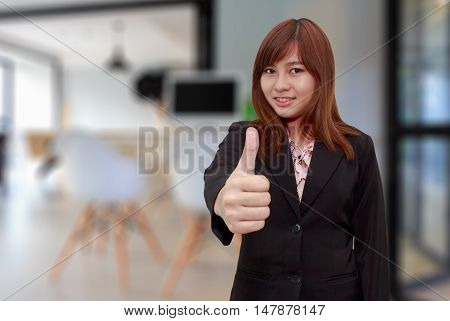Smiling businesswoman holding thumps up - feel good business concept.