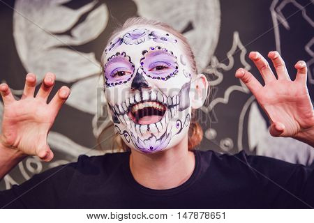 Girl with Halloween face art on a dark background with a pattern
