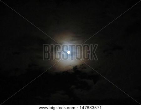 Dramatic photo of a nighttime sky with brightly lit full moon