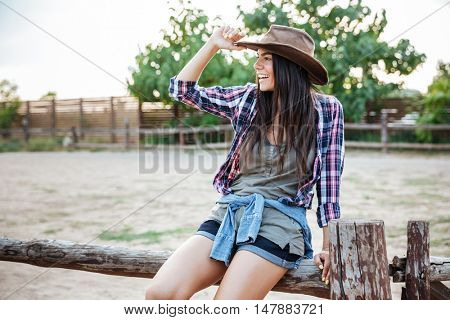 Portrait of cheerful relaxed young woman cowgirl sitting on fence and smiling