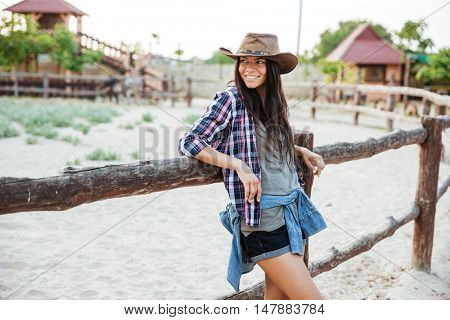 Smiling charming young woman cowgirl standing and leaning on fence