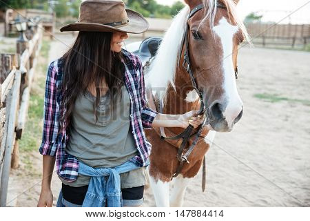 Smilng lovely young woman cowgirl with her horse in village