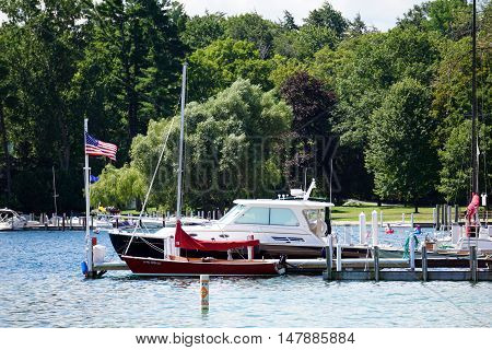 HARBOR SPRINGS, MICHIGAN / UNITED STATES - AUGUST 1, 2016: Boats are docked at a private pier next to the Zorn Park Public Beach in Harbor Springs.