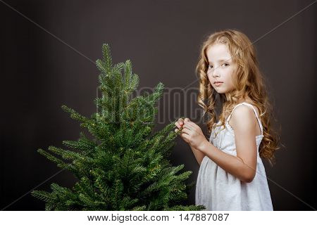 Bright little girl in white dress stands near the tree on the black wall backdrop