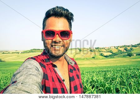 Young indian man taking selfie at green corn field with country hills background - Handsome african guy having fun using modern technology outdoors in a farmland -
