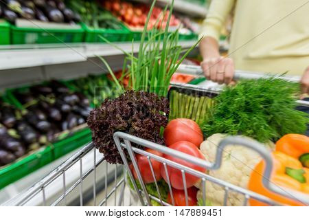 Closeup of a Customer Pushing a Shopping Cart Full of Groceries in a Supermarket
