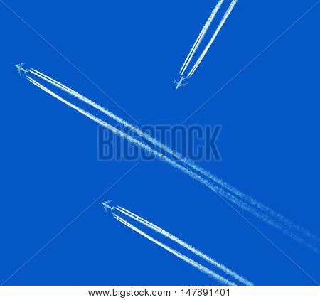 Planes with vapor stripes on the blue sky background
