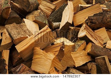 Large cut pieces of pine and birch firewood for the fireplace stacked in a pile. Interesting background and texture. Horizontal close view