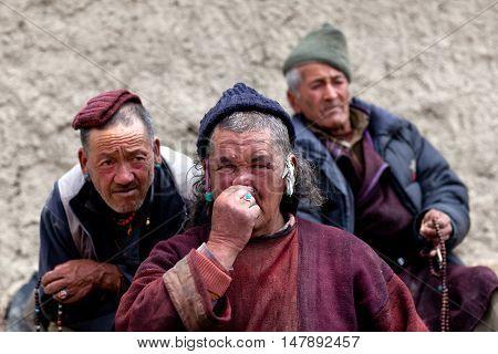 LAMAYURU, INDIA - JUNE 17, 2012: Three men praying in Lamayuru Gompa during Yuru Kabgyat festival