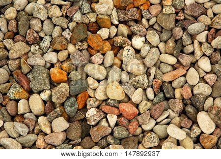 Flat surface with colorful fine pebbles of gravel. Interesting background and texture. Flat horizontal top view.
