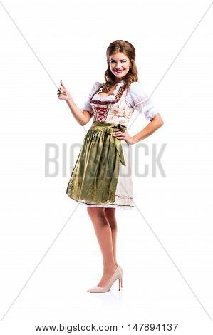 Beautiful young woman in traditional bavarian dress standing, hand on hip, thumb up. Oktoberfest. Studio shot on white background, isolated.