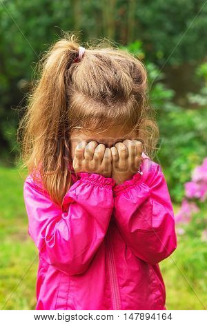 Unhappy cute baby girl is crying outdoors